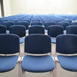 Empty auditorium chairs in rows.